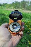 Compass in hand, against the background of blooming meadows. Stock Photography