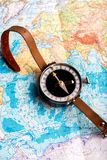 Compass in hand against the background of a bright world map royalty free stock photo