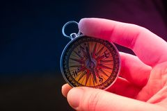 Compass in hand  as a concept of traveling and finding your life. Hand is holding a magnetic compass on black background stock images