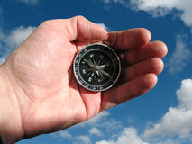 Compass in hand isolated. Compass in hand geographical, cartography, cartographical tools, insulated, sky background, for designer Royalty Free Stock Photos