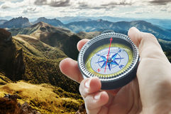 Compass and hand in mountains Stock Photo