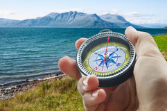 Compass and hand in mountains Stock Image