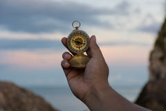 Compass in the hand on the nature  background. Compass in the hand on the nature background Stock Images