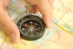 Compass in hand navigating on map pape. R Stock Image