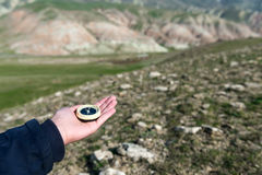 Compass in hand. Traveler in mountains with a compass Stock Photos