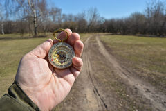 Compass in the hand on a walk. Royalty Free Stock Photos