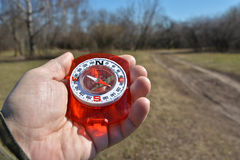 Compass in the hand on a walk. Royalty Free Stock Image