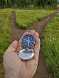 Compass Held Out At A Fork In The Trail Royalty Free Stock Photo