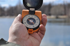 The compass in his hand outdoors. Stock Photography
