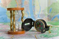 Compass and hourglass. On map background Royalty Free Stock Image