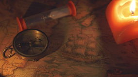 The compass and the hourglass near the candles. Two candles are lighted on the map stock video footage
