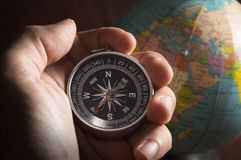 Compass in human hand with globe. Stock Photo