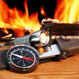 Compass,  hunting knife and  flashlight. Campfire in background. Stock Images