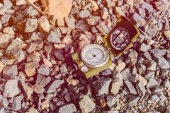 Compass instrument on gravel mountain hiking trail. Royalty Free Stock Image