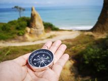Holding on a compass showing your direction and your navigation by facing to the ocean. A compass is an instrument used for navigation and orientation that shows stock photography