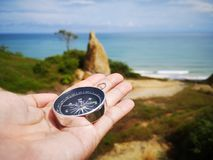 Holding on a compass showing your direction and your navigation by facing to the ocean. A compass is an instrument used for navigation and orientation that shows stock photo