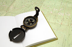 Compass on Journal. Compas sitting on journal on top of a Topography Map stock image