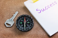 Compass with key and blurred text success on paper note, busines Stock Image