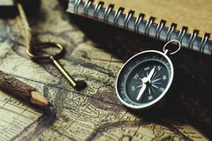Compass, key, pencil and book on blur vintage map background, retro classic color tone, copy space. Compass, key, pencil and book on blur vintage map background royalty free stock photo