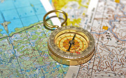 Compass laying on a topographic map. Royalty Free Stock Photo