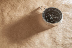 Compass on Light Brown Background Royalty Free Stock Image
