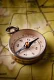 Compass lying on a map Stock Photos