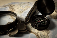 Compass with magnifier and ccoins on map Stock Photography