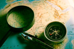 Compass with magnifier on map. Royalty Free Stock Image