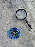 Compass and magnifier on sand stock images