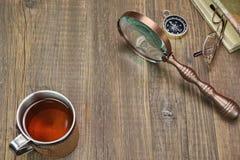 Compass, Magnifying Glass, Tea Mug, Two Notebooks on Wood Table Stock Photo
