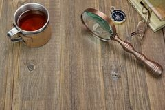 Compass, Magnifying Glass, Tea Mug, Two Notebooks on Wood Table Royalty Free Stock Images