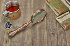 Compass, Magnifying Glass, Tea Mug, Two Notebooks on Wood Table Royalty Free Stock Photo