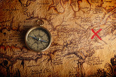 Compass and a map. Old brass compass lying on a very old map showing the way to treasure Royalty Free Stock Images