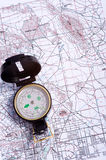 Compass on a map. A compass lying on top of a topographical map Royalty Free Stock Photo