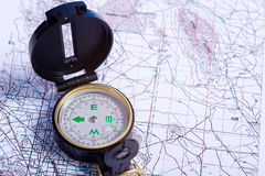 Compass on a map. A compass lying on top of a topographical map Stock Image