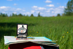 Compass and map on backpack. Compass and map lie on  backpack on  background beautiful nature Stock Photos