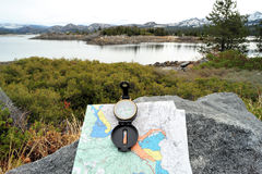 Compass, Map And Lake. A hiking map and compass overlooking a lake in the Califirnia sierra nevada mountains Royalty Free Stock Image