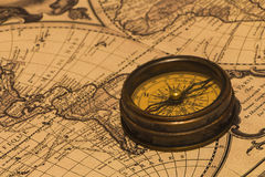 Compass on the map. The old brown metal compass on a world map background stock photos