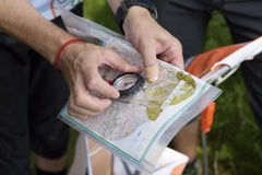 Compass and map for orienteering. Reading map. Man Selective focus Stock Image