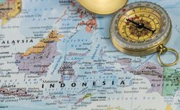 Compass on a close up map pointing at Indonesia and planning a travel destination. Compass on a map pointing at Indonesia and planning a travel destination stock photos