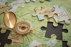 The compass on map. Vintage gold plated compass lying on the puzzle map Royalty Free Stock Image