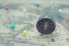 Compass and marking pins on blur vintage map, journey concept stock images