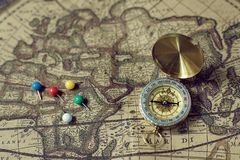 Compass and pins on blur vintage world map, journey concept, copy space. Compass and marking pins on blur vintage world map, journey concept, copy space Stock Photos