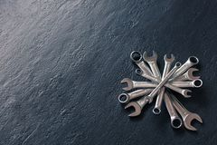 Compass of metal shiny wrenches on textured dark blue stone background. Stock Photography