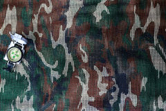 Compass on military camouflage net background Royalty Free Stock Photo