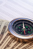 Compass On Money. Business concept. Closeup of compass and money on paper list with digits Royalty Free Stock Images