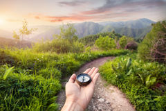 Compass in the mountains. Hand with compass at mountain road at sunset sky in Kazakhstan, central Asia