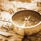 Compass on nautical map. Compass on surface of sepia historic nautical map Royalty Free Stock Photo