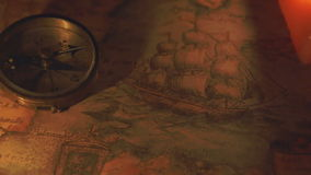 A compass near the two lit candles. Showing the shadow of the compass with the big boat drwaing on the map stock video
