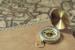 Compass and notebook on blur vintage world map, journey concept, copy space. Compass and brown notebook on blur vintage world map, journey concept, copy space Royalty Free Stock Photos